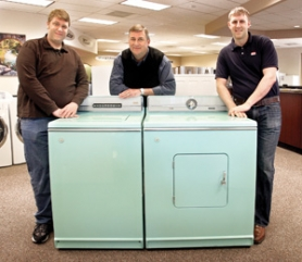 by: JIm Clark The second and third generations of the Riegelmann's Appliance store pose with a 1960 Maytag washer and dryer in the store's showroom. Jim Riegelmann, center, son of founder Neil is flanked by his sons Josh, left, and Mike.