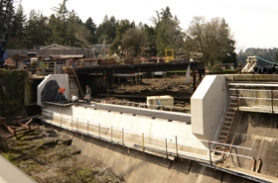 by: VERN UYETAKE Tuesday was a big day at Oswego Lake Dam as the gates were installed. Thanks to the new dam, the danger of flooding, as occurred in 1996, will be greatly decreased.