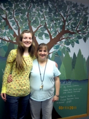 "by: Gus Jarvis Estacada High School Senior Anna Simmons is joined by Whispering Pines Administrative Assistant Sherri Schofield in front of Simmons' ""Tree of Life"" project."