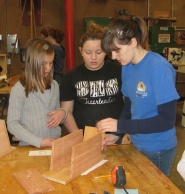 "by: Barbara Sherman WORKING HARD — Edy Ridge fifth-grader Josie Rutschman (left) works on her birdhouse with Sherwood High School sophomores Aspen LaMare and Sidney Franco during a joint workshop held as part of SHS's innovative engineering/construction class called ""No Boyz Allowed."""