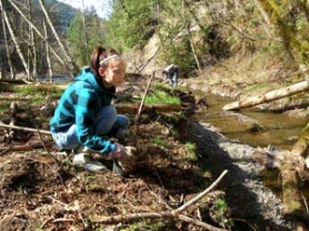 by: Russ Plaeger One of the students from a David Douglas High School natural resources class plants native vegetation along a side channel of the Salmon River in the Bureau of Land Management's Wildwood Recreation site. The class worked one Saturday each month to monitor and improve the site.