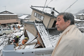 by: NICHOLAS KAMM A man looks on as U.S. rescue workers search for survivors in a house in Kamaishi, Iwate prefecture on March 16. The devastating earthquake is still producing ripple effects around the globe.
