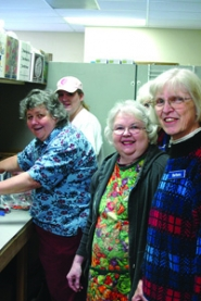 by: Gus Jarvis New Estacada Area Food Bank Executive Director Barbara Shibley, right, pauses for a moment on Friday with volunteers working during the food bank's open hours.