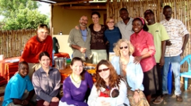 by: contributed photos Judy Beaudoin of Estacada (blond hair with sunglasses) gathers with friends after a meal at a refugee farm in Uganda.