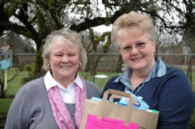 by: Gus Jarvis Linda Bagg (left) and Judy Brown hold a bag containing items families in need cannot purchase with food stamps.
