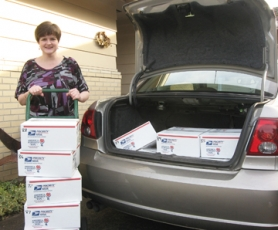 by: Barbara Sherman BOXES TO GO - Jennifer Fair gets ready to load more boxes into the family car to take to the post office for shipping overseas.