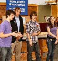 by: David F. Ashton PigMice lead programmer, Jared Milred, explains the nature of their robot's tasks to U.S. Senator Jeff Merkley, with the help of students Nathan Fuller and Mae Traham.
