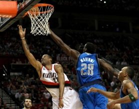 by: JAIME VALDEZ Trail Blazer center Marcus Camby gets behind Ian Mahinmi and the Dallas Mavericks defense for a layup in Sunday's Portland home win.