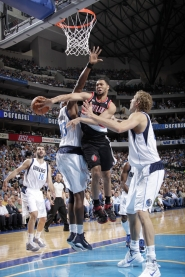 by: GLENN JAMES Trail Blazer guard Brandon Roy wraps a pass around Brendan Haywood of Dallas during Game 5 on Monday.