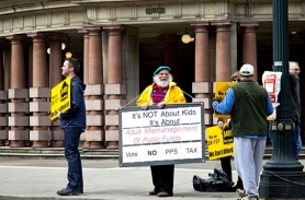 "by: Jennifer Hardin A small group led by activist Richard Ellmyer, center, gathered outside Portland City Hall Wednesday to protest the school bond and local option levy measures on the May ballot. The protest claimed the measures were ""a mismanagement of public funds."""