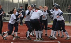 by: VERN UYETAKE Lake Oswego's softball team surrounds Verita Richardson at home plate after Richardson hit a grand slam against West Linn last week.