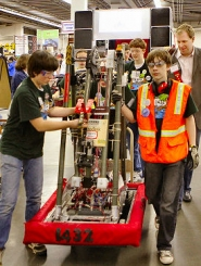 by: David F. Ashton Mahr's Metal Beavers rolls their robot out of the pit area. At the right rear is Oregon State Representative Jefferson Smith, admiring their machine.