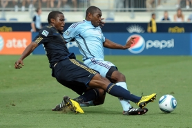 by: DREW HALLOWELL Danny Mwanga (left) of the Philadelphia Union gets off a shot around a defender in a 2010 MLS game against Colorado.