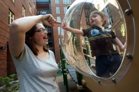 by: CHRISTOPHER ONSTOTT Janet Bailey and her son Nicholas, 17 months, play in the courtyard of the Ramona Apartments, the first affordable housing building in the Pearl District geared toward families and children.