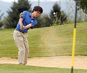 by: Miles Vance VC LEADER — Valley Catholic junior Greg Ong blasts out of a greenside bunker on Tuesday at Quail Valley Golf Course.