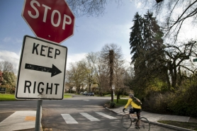 by: Jennifer Hardin A bicyclist pedals past the stop sign at Ladd Circle in Southeast Portland. Thousands of bicyclists cruise around the circle daily, traveling between the Hawthorne Bridge and the Clinton Street bike route.