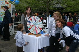 by: linda hundhammer Charlie Howell spins the prize wheel at the Lake Oswego School District Foundation booth at last Saturday's opening of the Lake Oswego Farmers Market.  From left, Patti Mertz, Sarah Howell, and Rhonda Cohen, LOSDF gave out more than 200 prizes throughout the day.