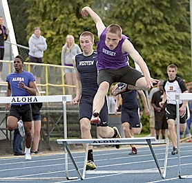 by: Miles Vance STILL GOING — Sunset's Eric Zechenelly hit the last hurdle but still won the district title on Friday.