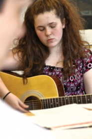 by: Cory Crouser Gresham High School freshman Arianne Melton plays in her acoustic guitar group, which meets after school. This is just one of her many activities, which she now has more time for after returning home from an international science fair in Los Angeles.