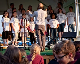 by: Alana Kansaku-Sarmiento Dan Ehrenfreund leads the members of the Errol Hassell Elementary School choir as they, like every other choir in attendance, sing songs meant to inspire hope for those affected by the tsunami in Japan.