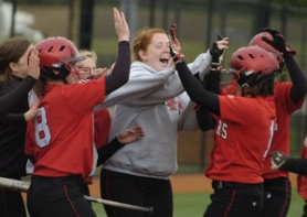 by: David Ball Sandy teammates celebrate with Becca Degner, right, after she knocked in the winning run with a line-drive single in the eighth inning Wednesday.