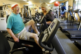 by: Jaime Valdez Wayne Hess, 76, works out in the fitness room of the Elsie Stuhr Center while bantering with Center Supervisor Linda Jo Enger. She says Hess makes the perfect poster boy for Older Americans Month in May.