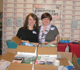 by: Barbara Sherman MANY MORE TO GO — Renee Atkins (left) and Jennifer Fair show off about 200 boxes representing how many they have shipped to soldiers overseas since last September.
