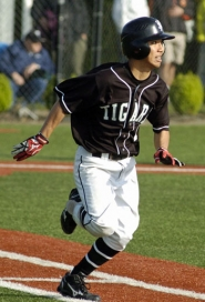 by: DAVID BALL ON THE GO — Tigard junior Hikaru Mizuno heads down the first-base line after one of his three hits.