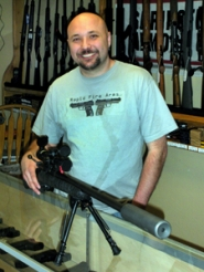 by: Jim Hart Brian Coleman, owner of Rapid Arms Gun Shop, is pictured behind the display counter with a silenced Remington Model 700 Varmit rifle with a telescopic sight calibrated for extreme accuracy with a specific bullet.