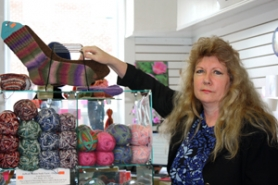 by: Lisa K. Anderson Sherri Anderson, owner of Designer Yarn in Sandy, shows some of the displays of colorful  and rare yarns in her store, where she she has an instructor teach classes in knitting and crocheting.