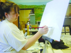 by: Arwen Ungar STEEP TO CLIMB — Graduating senior Kaitlin McIntyre, seen here painting a mountain scene, said she is concerned future art students won't have access to basic supplies.
