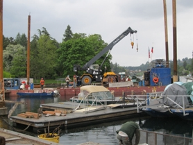by: SUBMITTED PHOTO Activity became intense in the closing days of the Lake Oswego Interceptor Sewer project. Here, a crane loads a barge at a trestle during the last week of in-lake work. The sewer is now complete.