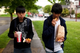 by: CHRISTOPHER ONSTOTT Franklin High School students Vu Bui (left) and David Corbin walk back to campus after buying corndogs, soda and jojos — foods they can't buy at school — from the nearby 50th Avenue Market.