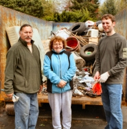 by: David F. Ashton Clean-up event chair Malcolm Hancock, volunteer Mary Miller, and the new Brentwood Darlington Neighborhood Association Chair, Chris Heart, show off one of the dumpsters on its way to being completely filled with refuse.