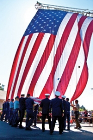 "by: AlANA KANSAKU-SARMIENTO The Patriot Flag, worn and patched from thousands of miles of travel and handling, flew over the Veterans Memorial with a flourish of students singing ""America the Beautiful""and a special reading of the Pledge of Allegiance."