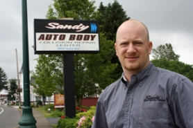by: Jim Hart Brandon Swan, owner of Sandy Auto Body, is pictured outside his business, which has been in its present location on Pioneer Boulevard since 1972. The business was selected as Pioneer Business for 2011.
