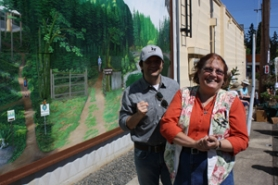 by: Jim Hart Former Mayor Linda Malone and City Attorney David Doughman react to the fact Malone's husband and mother (not pictured) were able to witness the dedication of a 60-foot mural to Malone in recognition of her service to the community for more than two decades.