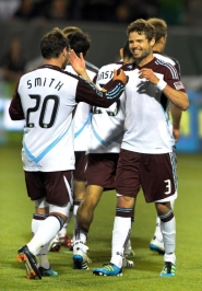 by: STEVE DYKES Drew Moor (right) of the Colorado Rapids gets a hug from Caleb Folan and congratulations from Andre Akpan after scoring Saturday night against the Timbers.