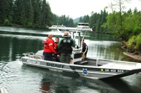 by: staff photo by GUS JARVIS Clackamas County Sheriff's Office Marine Patrol officers head back to where a body was found near the Estacada Lake boat ramp.