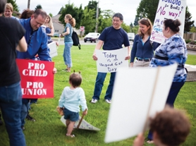 by: Chase Allgood Community members, including teacher's union president Jeff Matsumoto, right, gathered for a protest Monday before Forest Grove School Board members voted 4-1 to adopt a controversial budget for 2011-12.