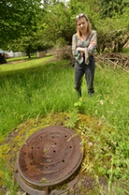by: VERN UYETAKE Carrie Beal stands next to a manhole in her backyard — evidence of the underground infrastructure the former paper mill needed to move effluent. Above ground, the area remains popular for wildlife, Beal said.