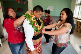 "by: Christopher Onstott Roosevelt High School graduate David ""Leka"" Koli gets help from cousins Talanoa Fukufuka and Pesi (who goes by a single name) at his family's traditional island celebration last Friday. ""I'm used to it,"" David says of the lavish affair. ""These are my people."""