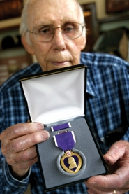 by: Jim Clark Tom Metzger holds the replacement Purple Heart medal given to the Gresham History Museum to replace an original medal that was stolen from the museum's military display in March.