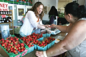 by: Jim Clark Katrina Ramsey helps a customer with her strawberry purchase at the Troutdale Fruit Stop on Friday,  June 17.