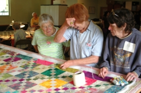 by: Gus Jarvis The Skip-A-Week Quilt Club members, from left, Penny Kampf, Bea Morales and Judy Terrill discuss a quilt at last week's meeting.
