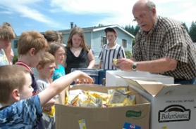 by: file photo Greg Lynch, the Estacada School District's operations director, hands out lunches to youngsters during last year's Summer Meal Program. The program reopened Monday.