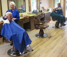 by: Barbara Sherman JUST A TRIM, PLEASE — (Foreground) Longtime King City barber Sandra Myers cuts the hair of Bob Santee, a Summerfield resident who is a longtime client, while in the background, Darlene Weil cuts the hair of Bill Saltzman of Tigard.