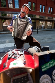 "by: CHRISTOPHER ONSTOTT Busker William ""Pug"" Bernhardt performs for tips at Saturday Market with a harmonica, an accordion, a bass drum, a snare drum and a cow bell. City officials say too many buskers are unaware of the requirement they play at one site no longer than one hour."