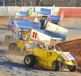 by: John Brewington MINI SPRINTS—Pacific Mini Sprint cars head into the first turn during racing at River City Speedway Saturday.