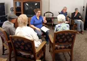 by: Jim Clark (Above) Kayla Shanks helps deaf residents with poor eyesight by interpreting for them during a resident council meeting at Chestnut Lane Assisted Living.